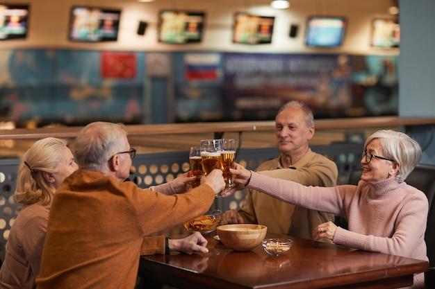 Gruppo di anziani sorridenti che bevono birra al bar e tintinnano bicchieri mentre si godono la serata con gli amici, copia spazio