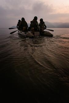 Un gruppo di soldati aiuta a remare in barca per mirare al crepuscolo, montagna sullo sfondo.