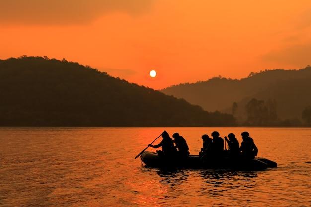 Un gruppo di soldati aiuta a remare in barca per prendere di mira il crepuscolo, la montagna e il sole sullo sfondo.