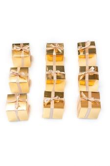 Gruppo di presente scintillante dell'oro o di contenitori di regalo in una fila con l'arco isolato