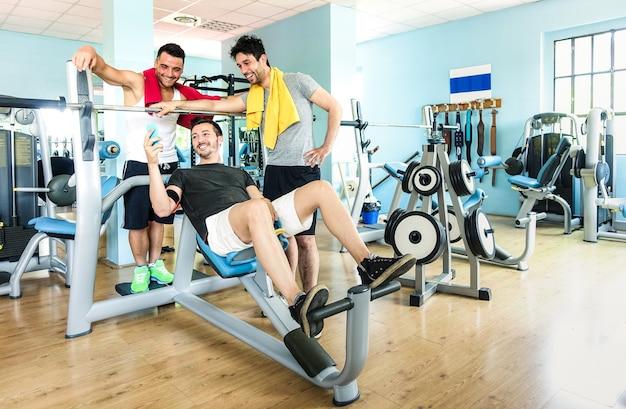 Gruppo di amici sportivi che utilizzano il telefono cellulare in palestra fitness club