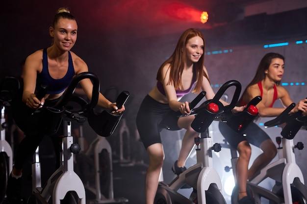 Gruppo di sportivi in palestra, persone muscolose dalla forma perfetta che si allenano in bicicletta, allenamento cardio in palestra, prendendo la perdita di peso con la macchina