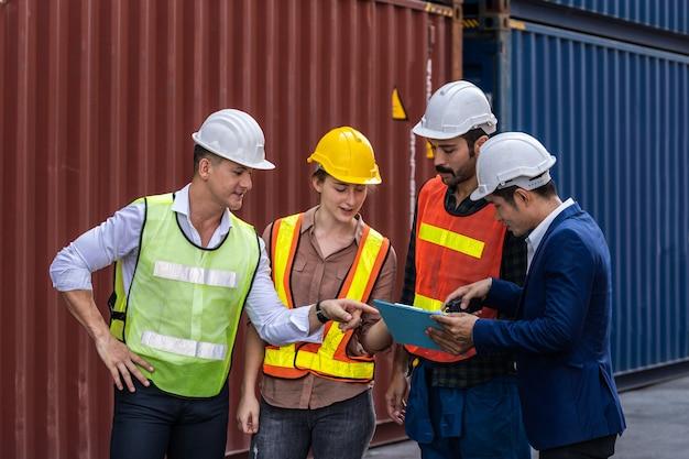 Gruppo di lavoratori del personale in piedi e controllando la scatola dei contenitori dalla nave da carico per l'esportazione e l'importazione
