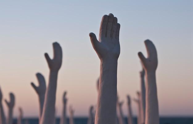 Un gruppo di statue che alzano le mani insieme