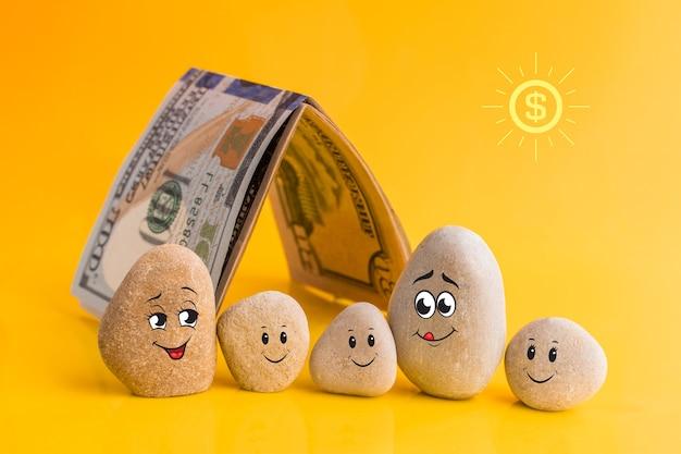 Gruppo di pietre con facce buffe disegnate e una casa fatta di soldi. padre, madre e i loro figli. famiglia con un buon piano finanziario. investimento, deposito bancario, concetto di gestione del denaro.