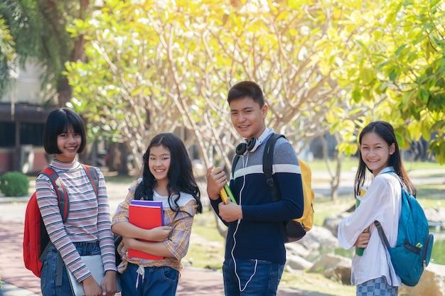 Il gruppo di giovani felici dello studente che cammina all'aperto, diversi giovani studenti prenota all'aperto concetto