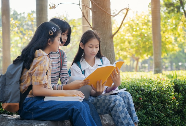 Raggruppi i giovani dello studente e il libro di lettura di istruzione nel parco della città Foto Premium