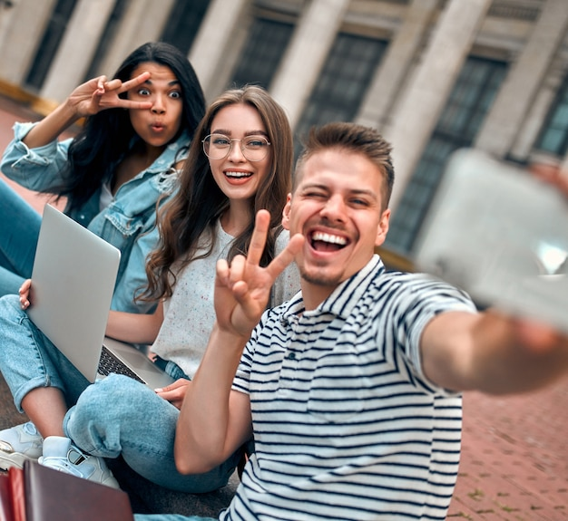 Un gruppo di studenti è seduto sui gradini vicino al campus con i laptop, si rilassa, chiacchiera e si fa selfie su uno smartphone.
