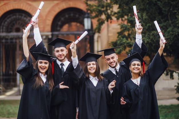 Gruppo di studenti che frequentano la cerimonia di laurea. bella giornata