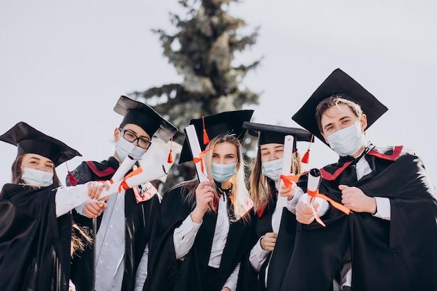 Gruppo di studenti che festeggiano insieme la laurea e indossano maschere per il viso