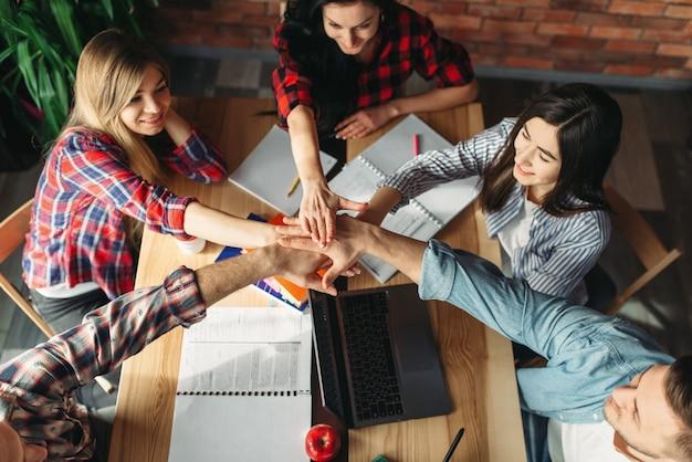 Un gruppo di studenti ha stretto le mani sul tavolo