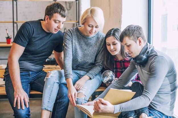 Un gruppo di amici studenti stanno facendo e discutendo idee creative nel loft
