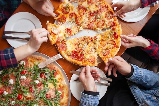 Gruppo di amici studenti mangiano pizza italiana, le mani prendono fette di pizza in un ristorante