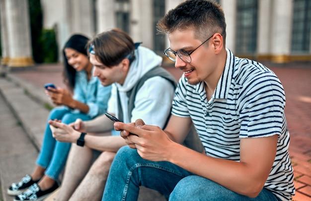 Un gruppo di studenti si siede sui gradini fuori dal campus e utilizza i propri smartphone.