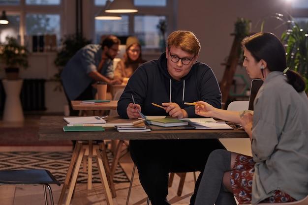 Gruppo di studenti seduti al tavolo con libri di testo e lavorano in team