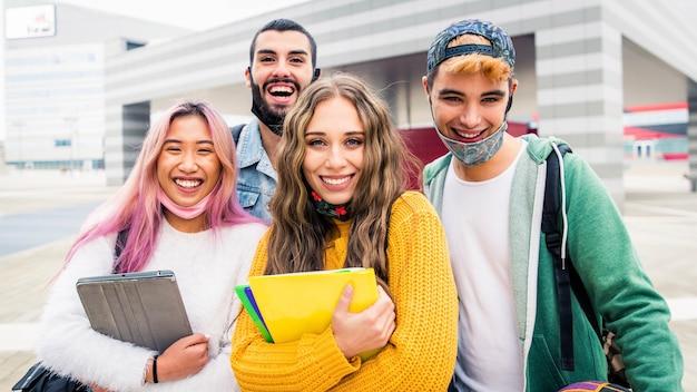 Gruppo di studenti che indossano una maschera protettiva che sorridono alla telecamera - concetto di ritorno a scuola