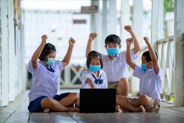 Un gruppo di studenti che indossano una maschera protettiva per proteggersi dal covid-19 utilizza il laptop per avere lezioni online felicemente nell'aula della scuola thailandese.