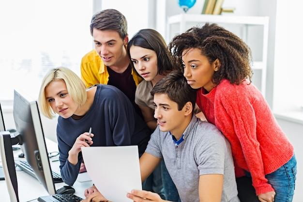 Gruppo di studenti con computer a lezione in aula