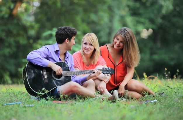 Un gruppo di studenti con una chitarra si rilassa seduti sull'erba nel parco cittadino.