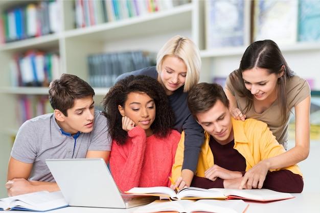 Gruppo di studenti con laptop e libro che fanno lezioni