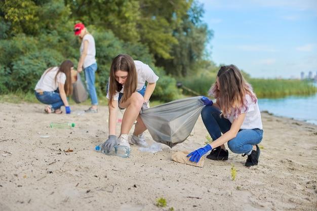 Gruppo di studenti con insegnante in natura che fa la pulizia dei rifiuti di plastica. protezione dell'ambiente, gioventù, volontariato, beneficenza ed ecologia