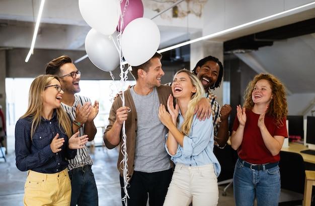 Gruppo di uomini d'affari di successo in ufficio che celebrano i profitti e il team building
