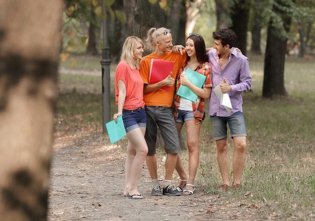 Gruppo di studenti di successo in piedi in un parco cittadino.