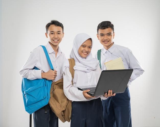 Gruppo di adolescenti che indossano uniformi scolastiche utilizzando un computer portatile insieme mentre trasportano uno zaino ...