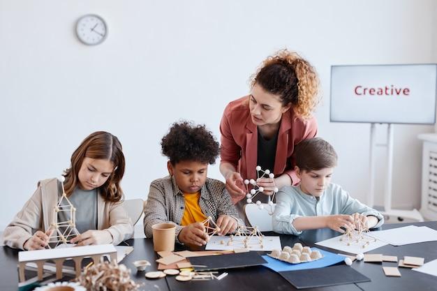 Gruppo di tre bambini che realizzano modelli in legno durante la lezione di arte e artigianato a scuola con insegnante femminile