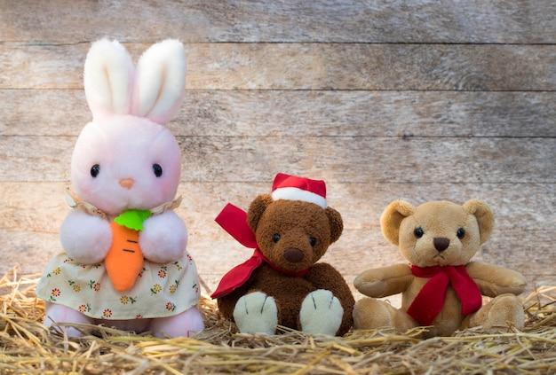 Un gruppo di tre bambole carine e soffici su uno sfondo di paglia e legno Foto Premium
