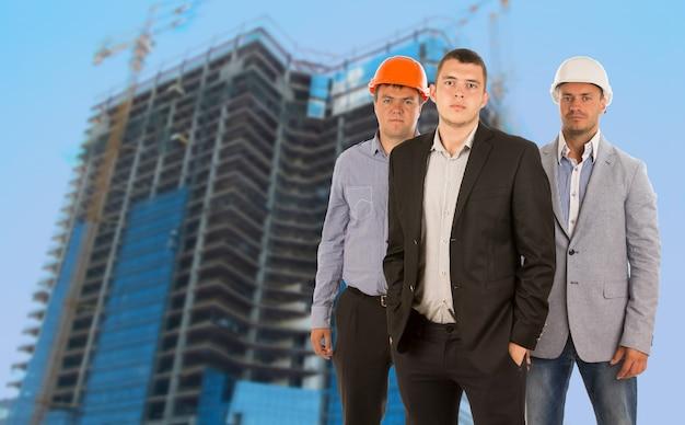 Gruppo di tre ingegneri e architetti nei loro elmetti protettivi in piedi raggruppati davanti a un grattacielo