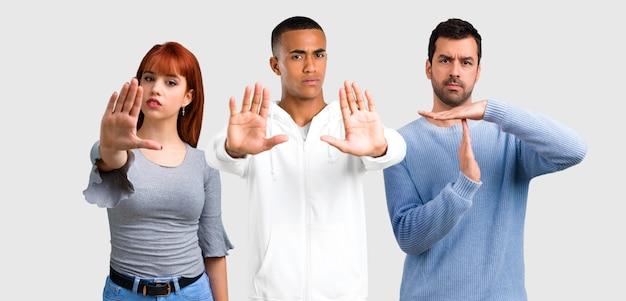 Un gruppo di tre amici che fanno il gesto di arresto con la sua mano Foto Premium