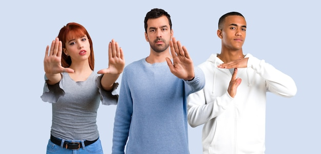 Un gruppo di tre amici che fanno il gesto di arresto con la sua mano