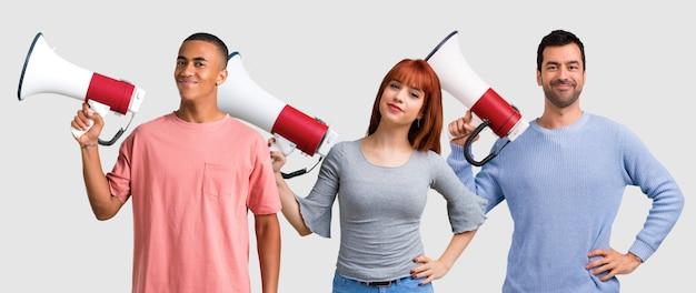 Un gruppo di tre amici che gridano tramite un megafono