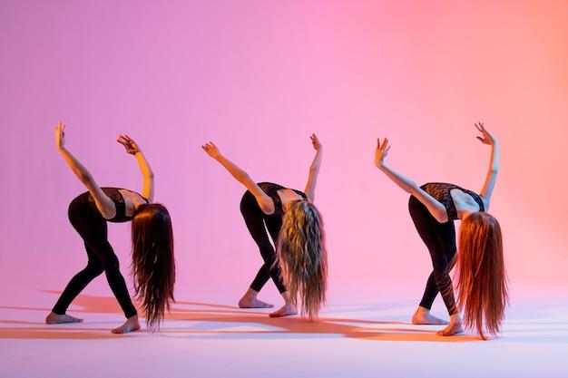 Un gruppo di tre ragazze in abiti aderenti neri che ballano su uno sfondo rosso