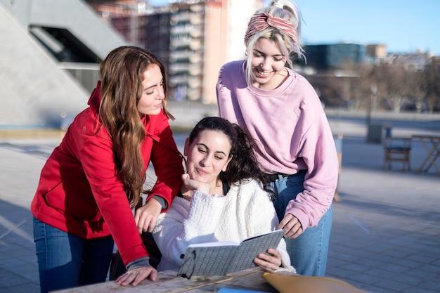 Un gruppo di tre amiche felici che ricordano i loro tempi passati mentre leggono insieme un libro del diario, hanno sorpreso e ridendo