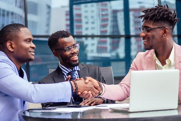 Un gruppo di tre eleganti uomini d'affari afroamericani amici imprenditori moda abiti da lavoro riunione seduti al tavolo e stretta di mano in un caffè estivo all'aperto. concetto di buon affare di successo.