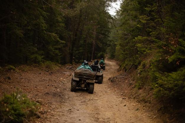 Un gruppo di turisti su atv attraversa la foresta gli atv sporchi guidano fuoristrada