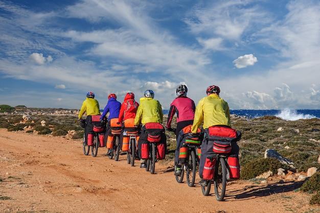 Un gruppo di ciclisti turisti va in mountain bike con grandi zaini lungo il mar mediterraneo sull'isola di cipro
