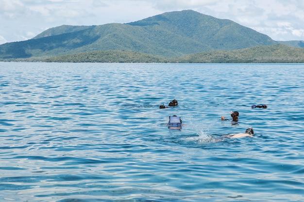Gruppo di turisti che nuotano e fanno snorkeling in mare con vista sulla montagna verde a karimun jawa