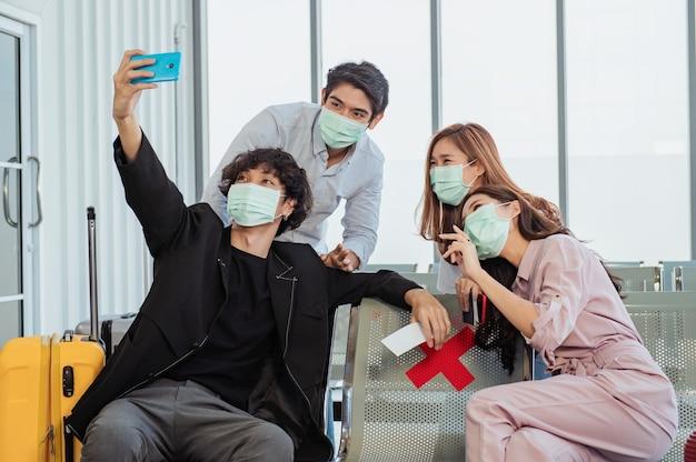 Gruppo di turisti che si fanno un selfie in aeroporto prima del volo