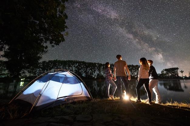 Gruppo di turisti con tenda sulla riva del lago di notte