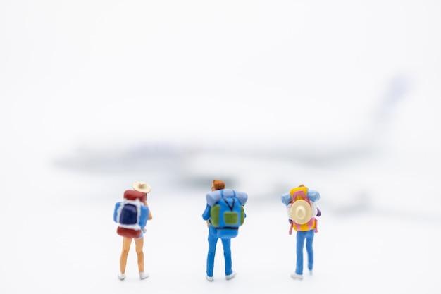 Gruppo di figura miniatura del viaggiatore con lo zaino che sta sul bianco con l'aeroplano del mini giocattolo.