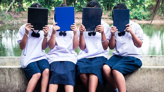 Il gruppo di studenti uniformi che tengono il libro. concetto di migliori amici