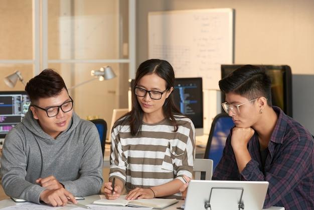 Gruppo di studenti universitari che disegnano una chat di flusso e discutono dell'architettura del software quando si lavora su un progetto di squadra