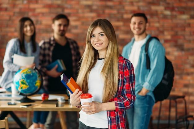 Gruppo di studenti universitari con libri di testo in piedi presso il muro di mattoni.