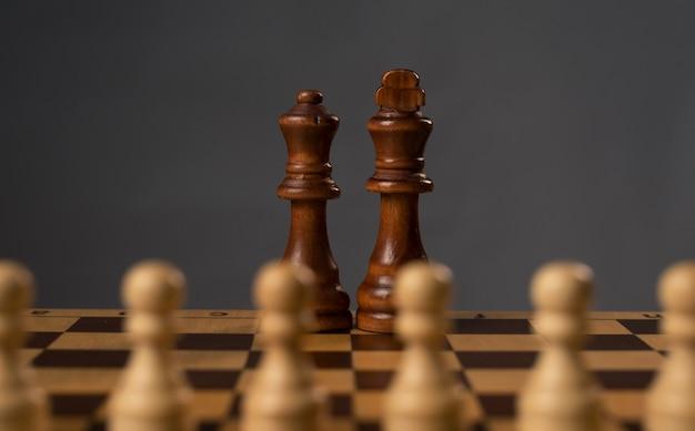 Gruppo di pedine bianche che lottano contro il re e la regina di legno neri sulla scacchiera.