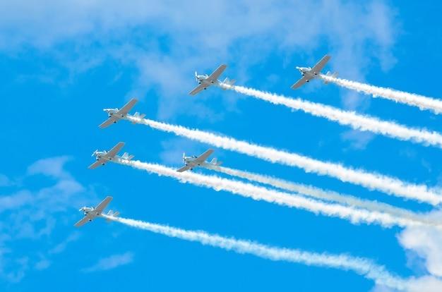 Gruppo di aerei a turboelica bianchi con una traccia di fumo bianco contro un cielo blu.