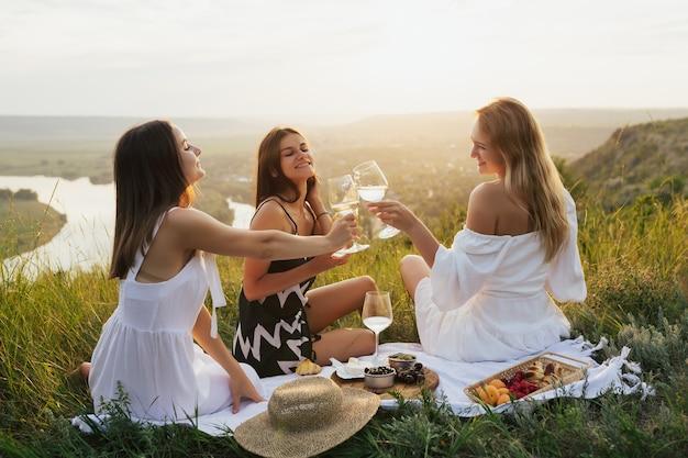 Un gruppo di amici della donna sta facendo picnic all'aperto. loro si divertono.