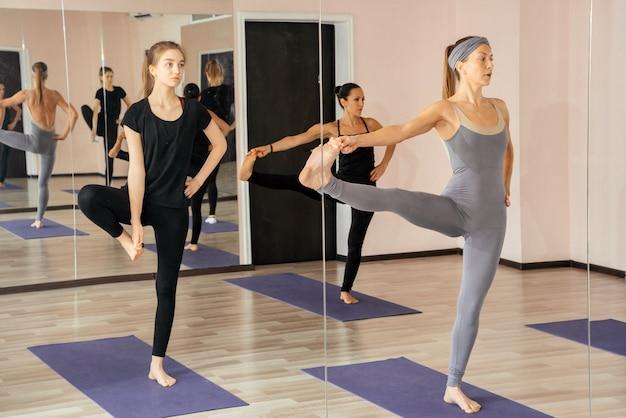 Gruppo di donne che fanno yoga posa in studio, facendo esercizi sportivi insieme
